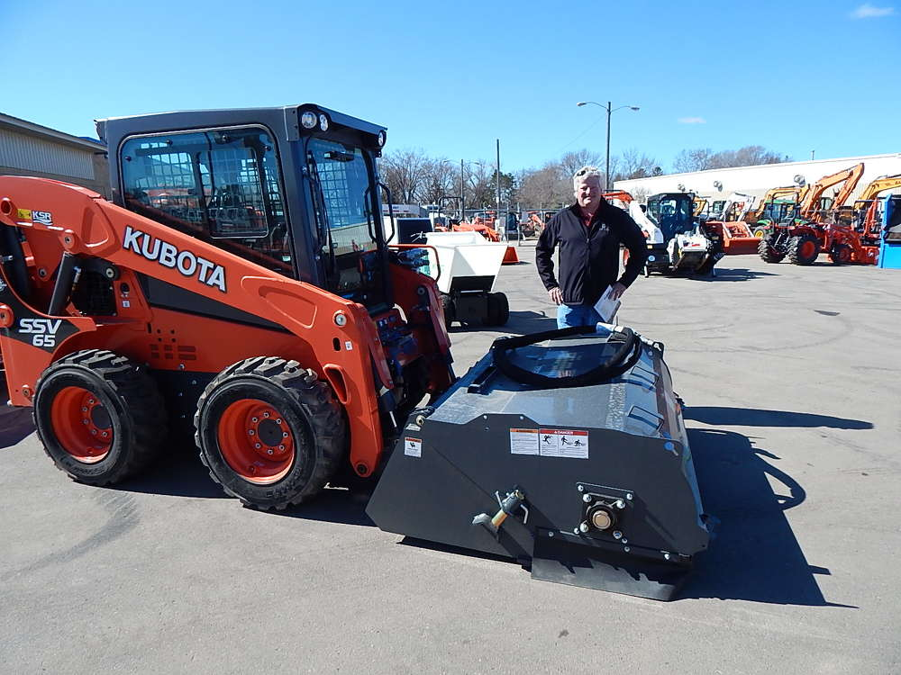 Joe Shaughnessy, Virnig Attachments product representative, Rice, Minn., showcases  a Virnig 72 in. pick up broom on a Kubota SSV65.