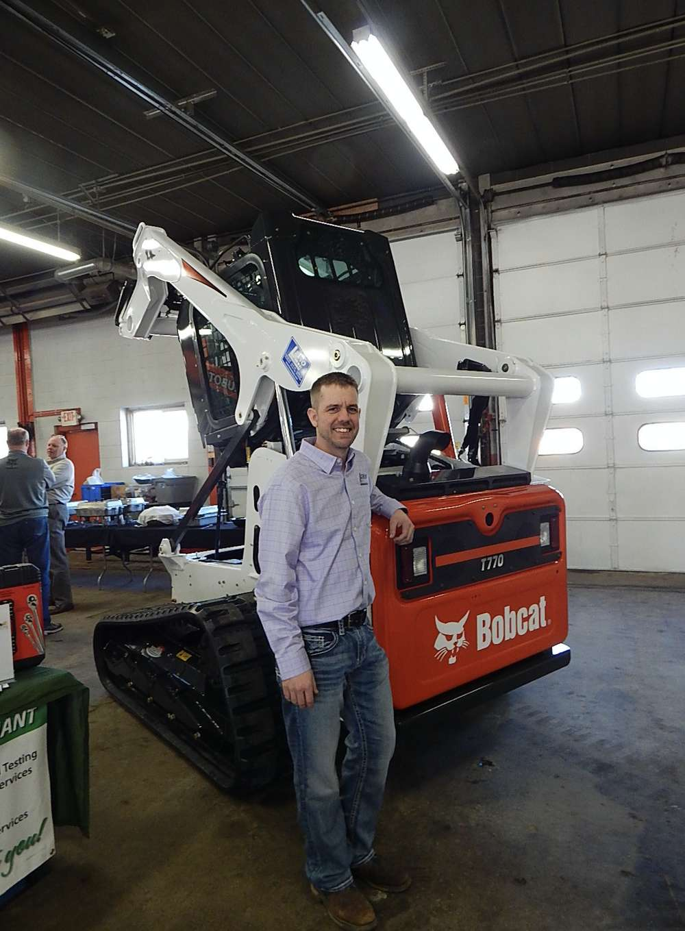Ryan Sabre, store manager of Lano Equipment Inc., Anoka, Minn., greets guests in front of a Bobcat T770 track machine.