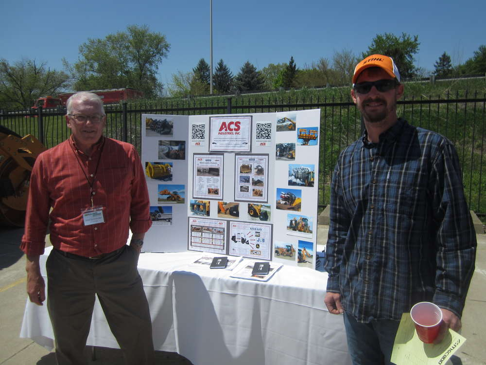 Mel Schnindler (L), ACS Industries, showcases the company's many attachments to Neil Anderson of Clarion Construction.