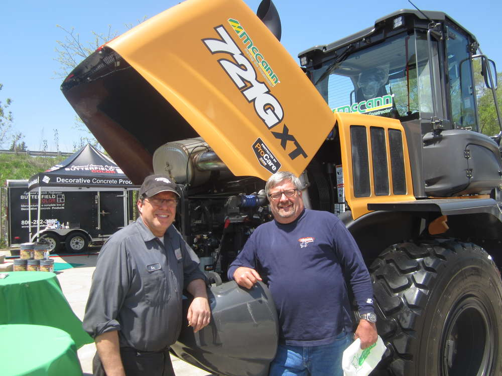 Ken Joniak (L) and Bill Schneider, both of Windy City Truck Repair, look at the engine of this Case 721G XT wheel loader.