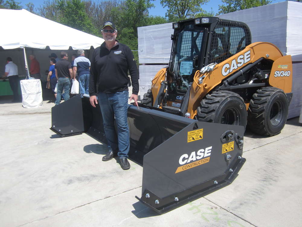 Wayne Smith, Arctic Snow & Ice Control, stands in front of the 10-ft. sectional pusher attached to a Case SV340 skid steer.