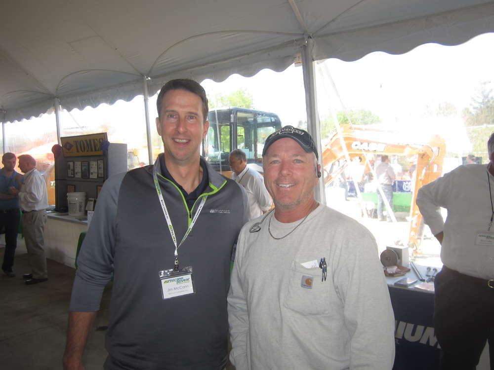 Jim McCann (L), president and CEO of McCann Industries Inc., welcomes John Pittman, Abel Concrete Inc., to the pig roast and open house.