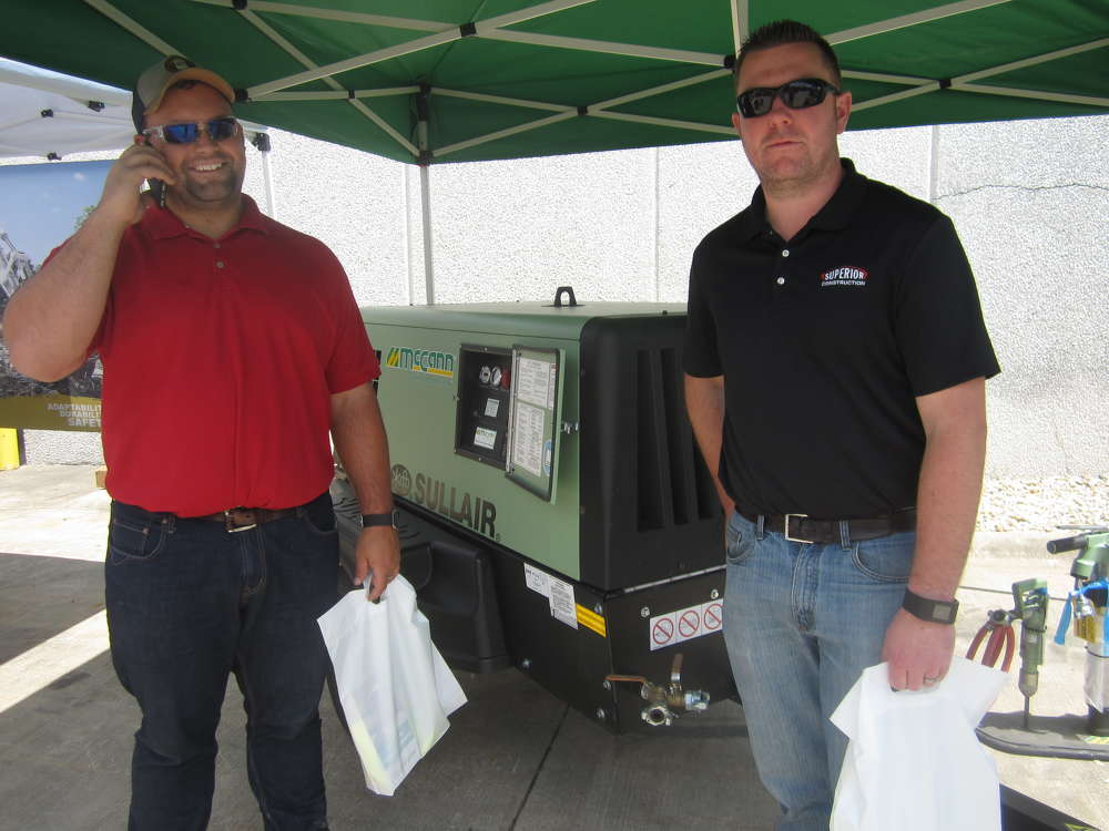 Phil Terhaar (L) and Brian Connolly, both of Superior Construction, take a look at this Sullair 185 air compressor.