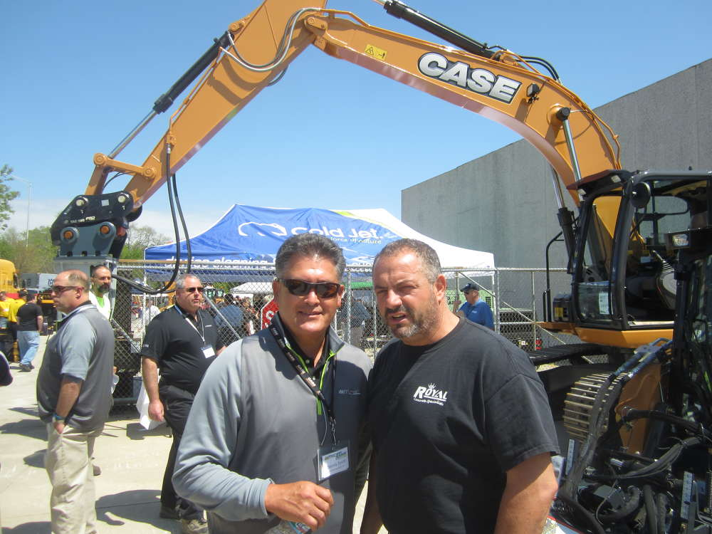 Dennis Tovar (L), McCann Industries Inc., talks about the company's equipment lines with Salvatore Giovine, Royal Concrete Specialties.