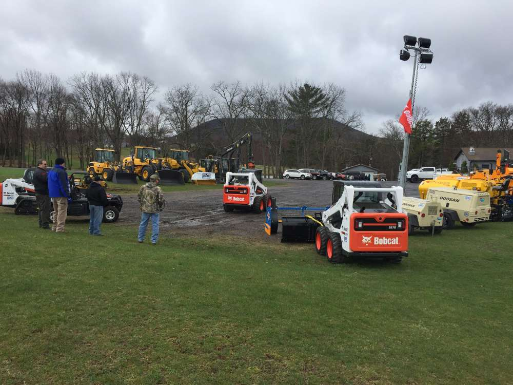 Guests look over the lineup of construction equipment Highway offers