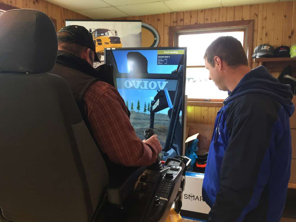 Jason Bissol (R), product support representative, shows a customer how to man the Volvo excavator simulator