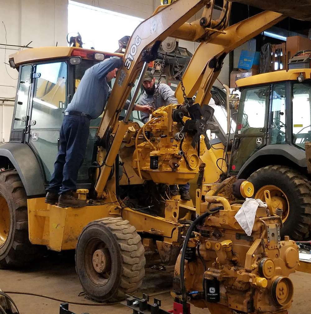 Mark Salvaryn (L) and Jason Edwards install a new engine in a John Deere 310G backhoe