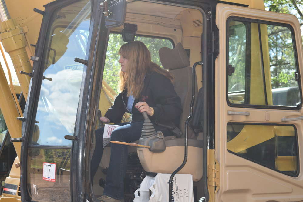 Karen Abbott, sales, Abbott Equipment Sales in Lebanon, Maine, tries out this Caterpillar 315B excavator during the auction.