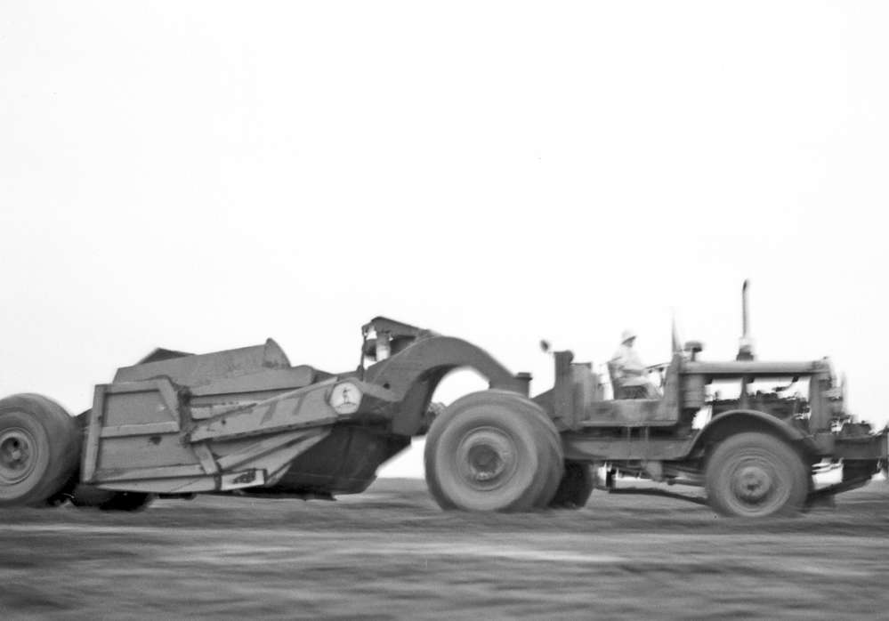 Akron University photo One of the 16 three-axle Euclid pan scrapers used for earthmoving on the project speeds back to the cut section in this 1954 photo.