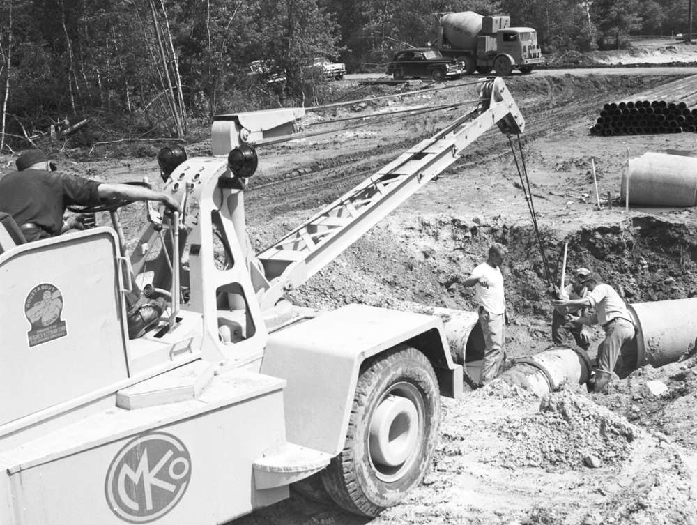 "Akron University photo A Hughes Keenan Roustabout ""pocket crane"" sets reinforced concrete drain pipe."