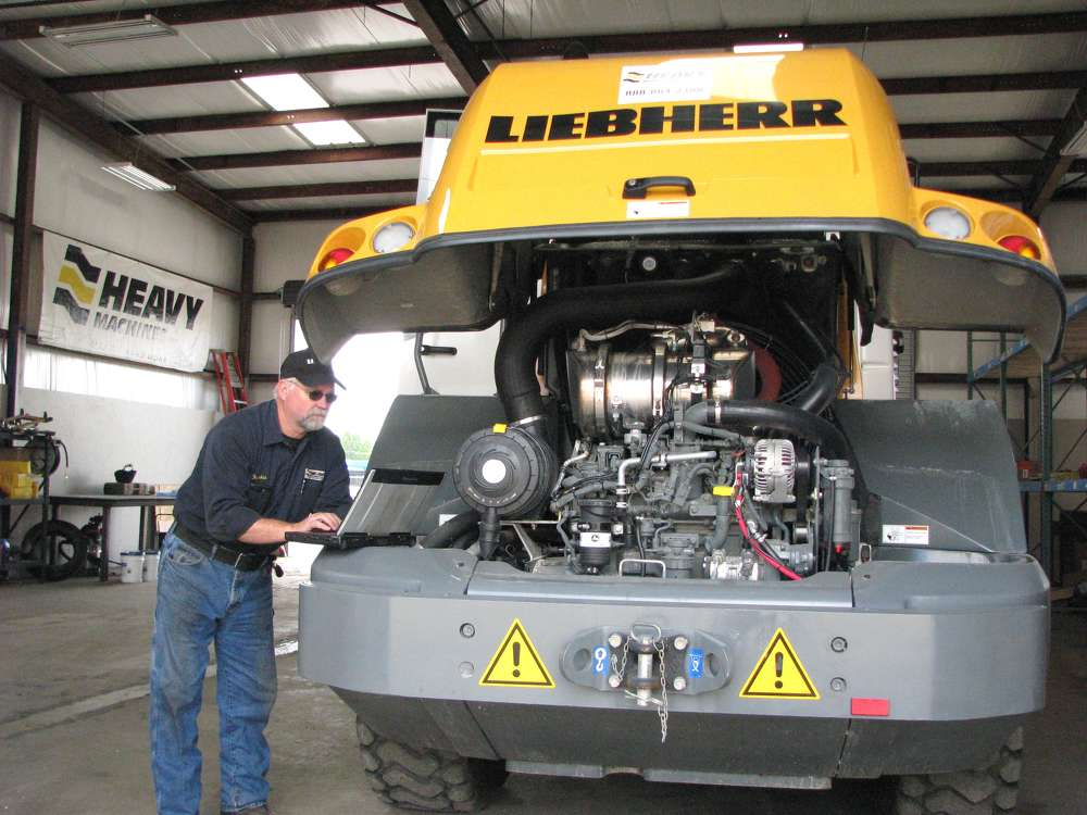 Frankie Raney, HMI service tech, performs diagnostic work on a Liebherr 528 wheel loader in the shop area.