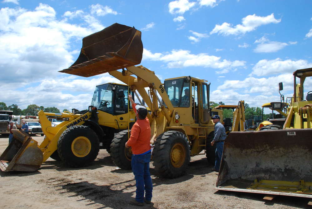 A customer takes measurements on this 1991 Caterpillar 916 wheel loader.