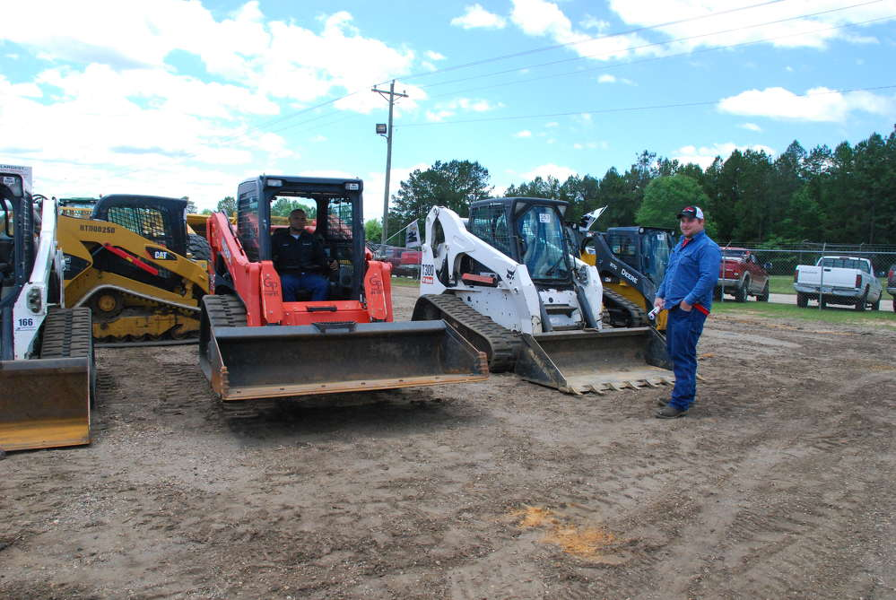 Adam (L) and Dennis Warren of Arkansas get a closer look at the selection of skid steers.