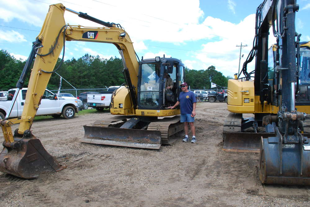 David Scarbarough (L) and Jamie Luzenberg from Saucier, Miss., inspect a 2007 Caterpillar 308CR mini-excavator.