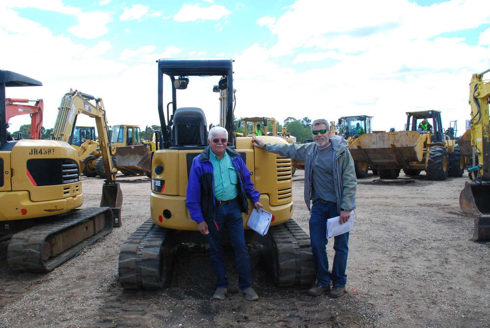 Ronnie (L) and Donnie Foley from Robertsdale, Ala., show interest in this 2014 Caterpillar 305ECR mini-excavator.
