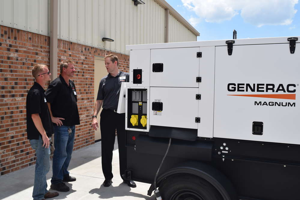 Jody Wall (R) talks about the features and benefits of his Generac Magnum Generator to Logan Siudak (L) and Chuck Siudak of Essian Construction of Altamonte Springs, Fla.
