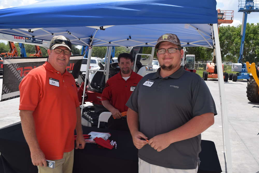 Joe Barrett (L) and  Jake Strickland (R), both of Barrett's Equipment, talk with Steve DePriest, regional sales manager of Takeuchi about the Takeuchi equipment line.