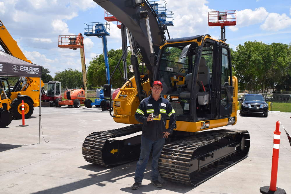 Zach Oehmke of Tomahawk Construction stands in front of this John Deere 135G excavator, holding his prize for being the winner of the John Deere experience at the event.