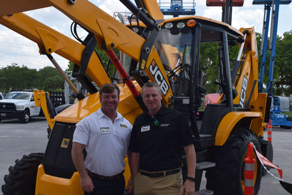 Patrick Smith (L) of JCB and Bryan Kiser, vice president of sales, H&E Equipment, greet customers at the event.