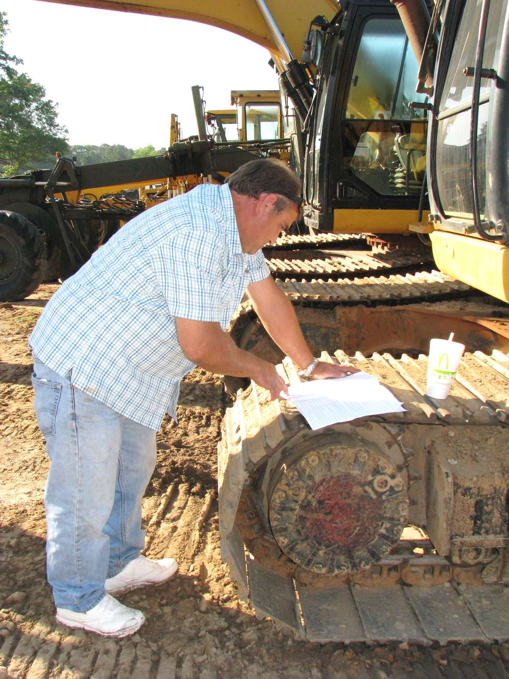 Jeff Stewart of J & S Farms, Toccoa, Ga., reads up on the excavators listed in the bidder's catalogue.
