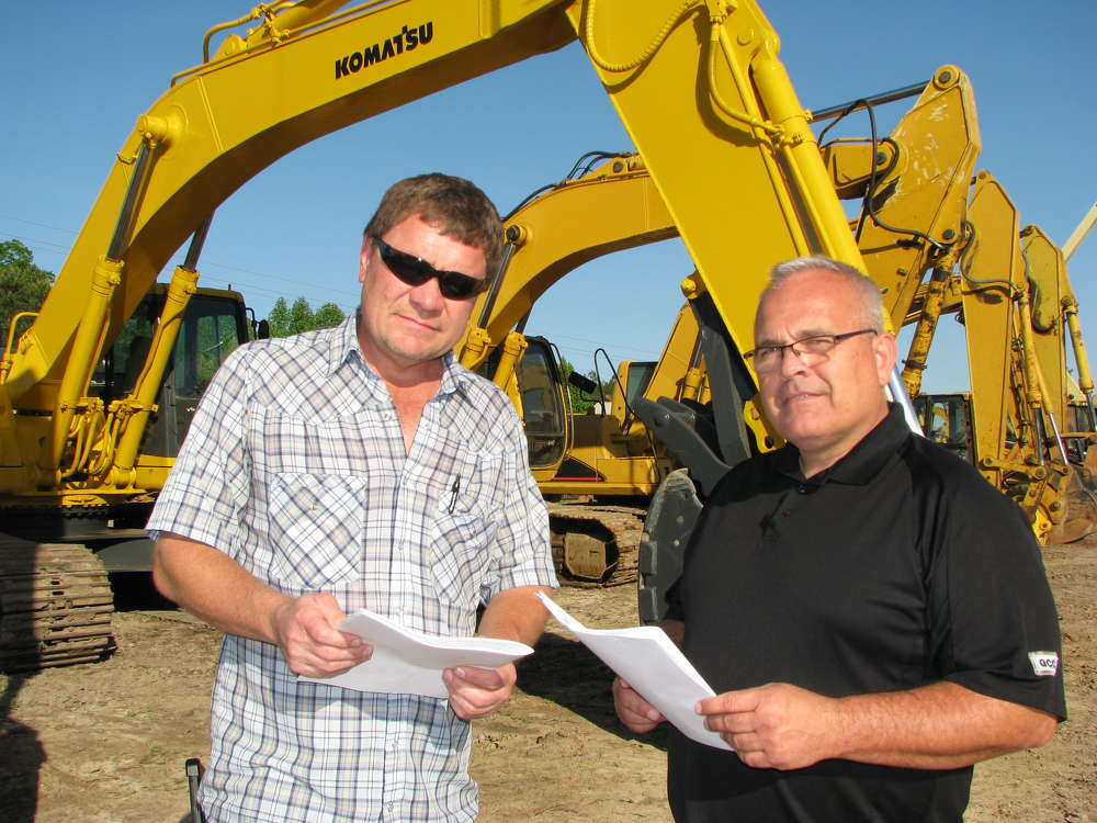 Vance Terry (L) and Bryan Boyd, both of Gunter Construction, Lawrenceville, Ga., check  out the excavators.