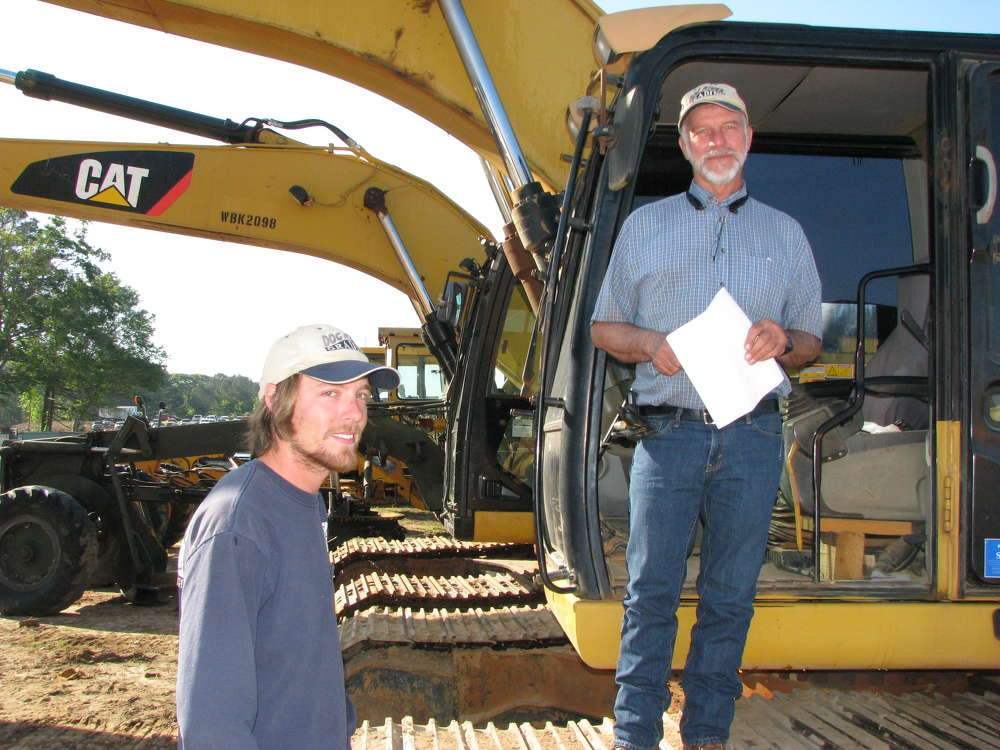 Logan (L) and Jerry Turner, both of Dog River Grading, Carrollton, Ga., hope for a bargain price on this Cat 320 excavator.