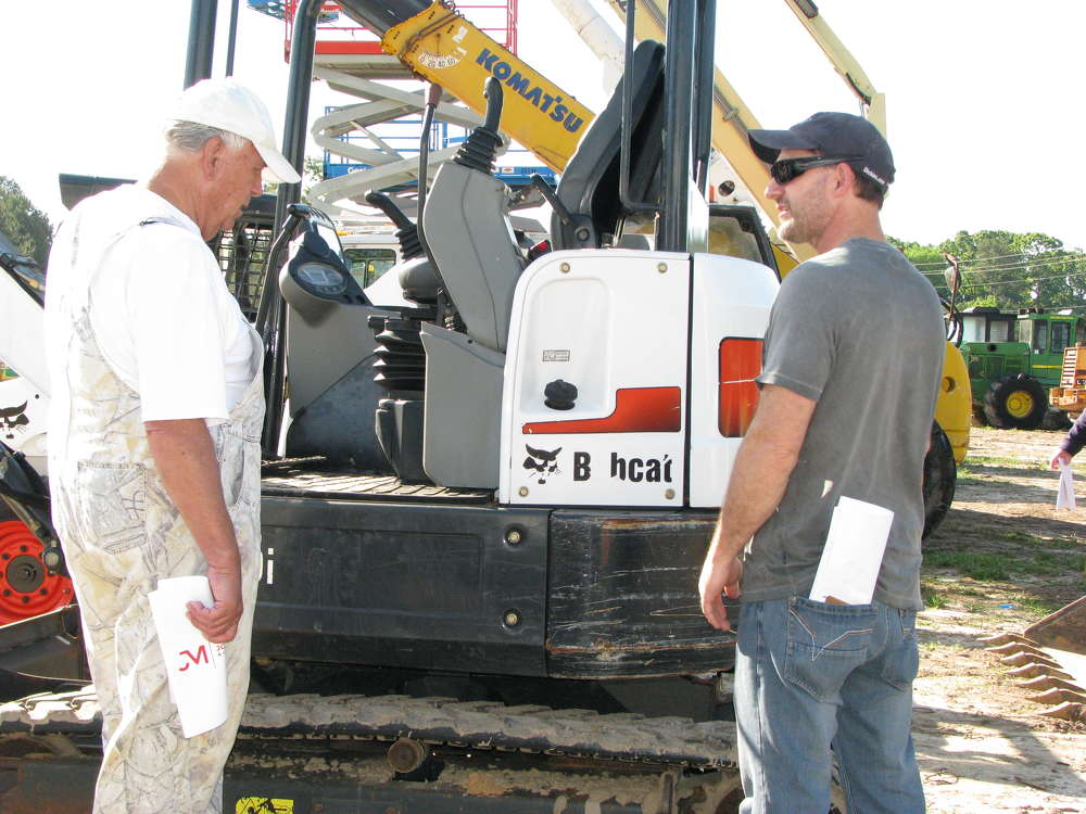 Jerry Cox (L), a farmer in nearby Anniston, Ala., and Robert Timms, Magic Rooter, Buchannan, Ga., discuss some of the Bobcat machines about to go on the auction block.