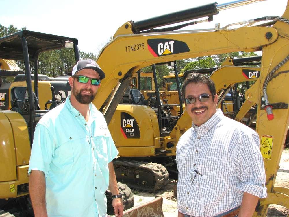 Thomas Davis-Cox (L), Joey Martin Auctioneers, and Jesus Ramirez of Vesco Tractor, Gadsden, Ala., attend the auction.