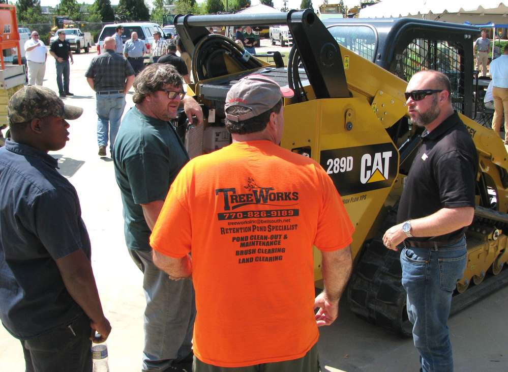 Yancey's Phillip Martin (R) provides a complete walk-around demo of a Cat 289D compact track loader with several attendees.