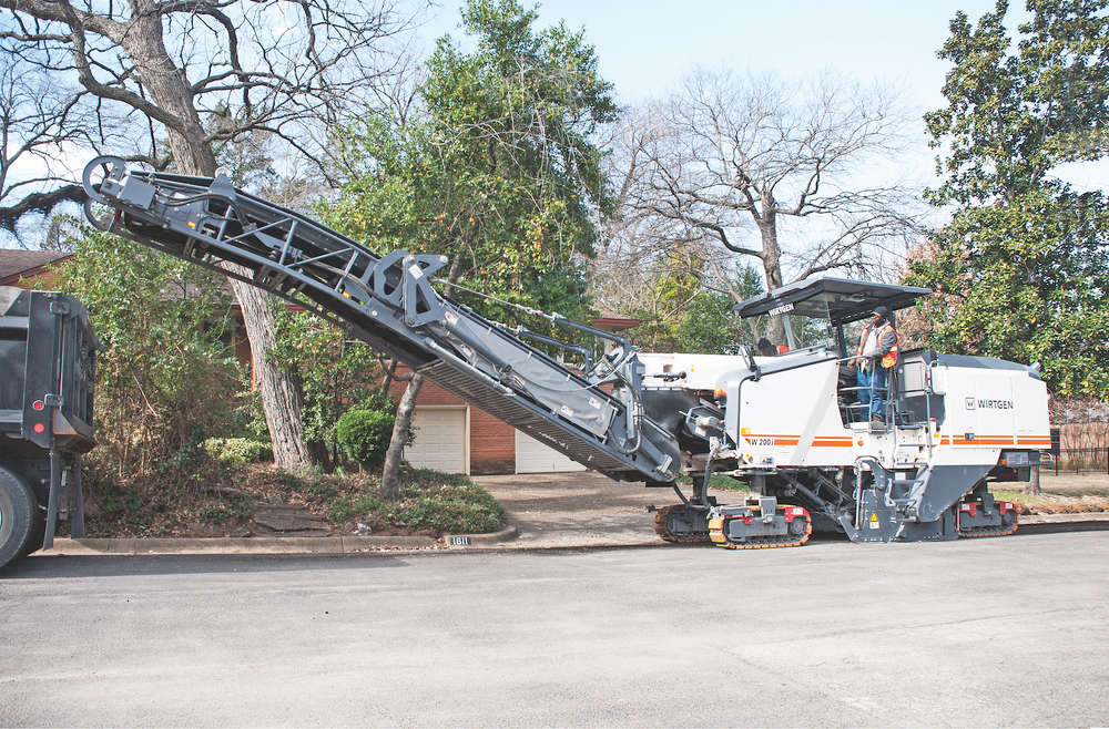The city of Dallas mobility & street services department equipment operator Charles Edwards guides a new Wirtgen W 200i milling machine along a residential street to remove old asphalt. The city purchased several pieces of Wirtgen Group equipment (Hamm, Wirtgen and Vögele) from Kirby-Smith Machinery to help with street repair and maintenance