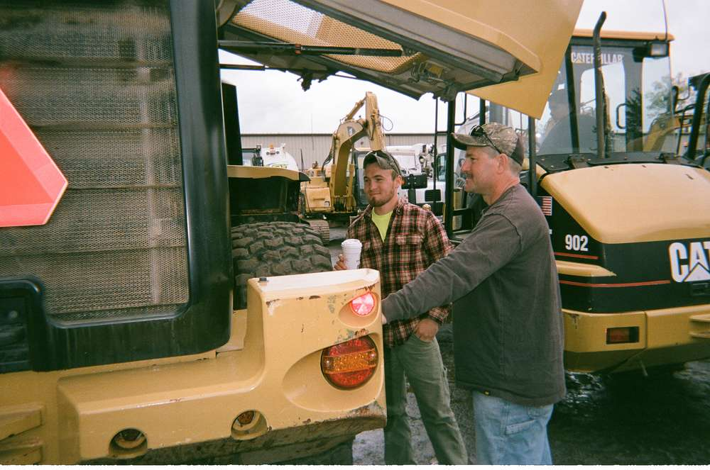 Steven Pollansky (R) and his son, Andrew, of Pollansky Construction, Coventry, Conn., look at various heavy iron up for bid.