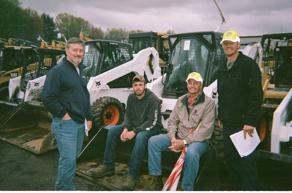 Three generations of the Marion family sit on an excavator as auctioneers called the auction of more than 1,100 individual lots. The owners of Marion Excavating of South Hadley, Mass., include Todd, his uncle, Russ, and sons, Mark and Reed Marion. Marion Excavating has been in operation for 45 years.