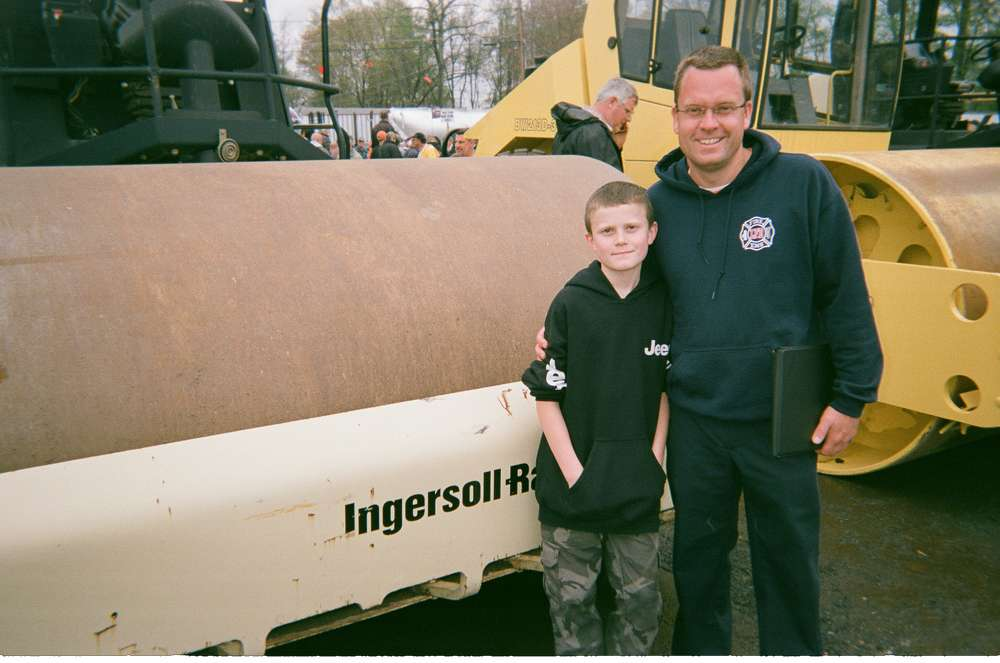 Eric Jakubowicz and his son, Logan, of Brookside Equipment Sales Inc. of Phillipston, Mass., look at a roller up for bid.