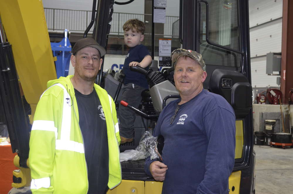 (L-R) are Richie Pierce, owner of R.A. Pierce Trucking; Richie's son, Colton, in the driver's seat; and Paul Sylvia, owner of Sylcon Excavating in Lincoln, Mass.