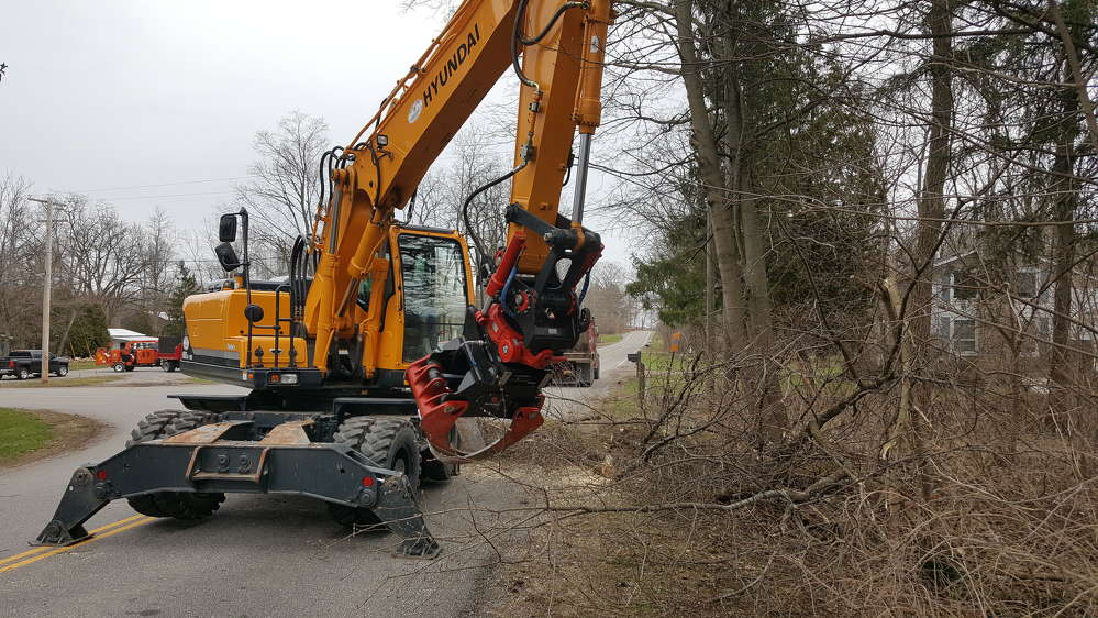 The Hyundai 180W-9A 38,000 lb. wheeled excavator equipped with a Rototilt RT60 rotating coupling system being used to clean up brush.