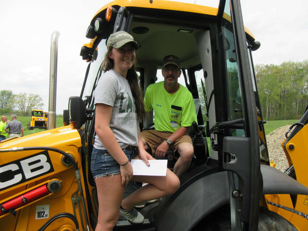 Doug White of East Fallowfield Township and his daughter, Jillian, demo a brand new JCB model 3CX backhoe similar to the one they have back home.