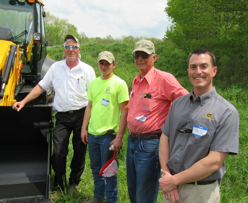 Walsh Equipment's Tim Gold (L) and Charlie Walsh (R) talk JCB backhoes with Summerhill Township's Adam Sherman and Bob Arendash.