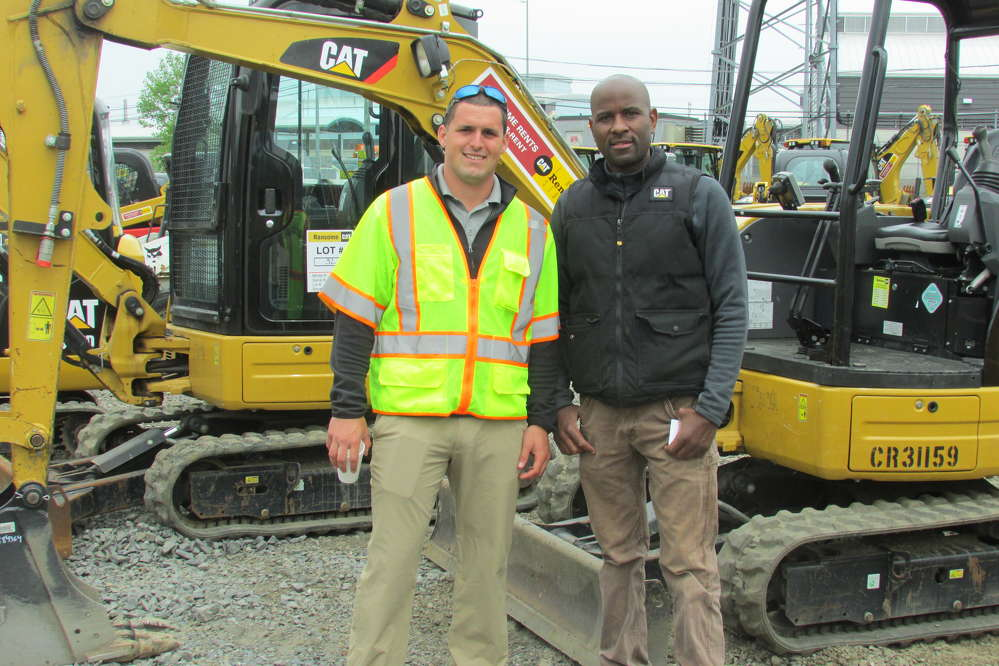 Nick McPeak (L), equipment specialist of Ransome CAT, and John Haye, owner of Haye Construction, Philadelphia, Pa., talk about the features of the Caterpillar 303.5 mini-excavator.
