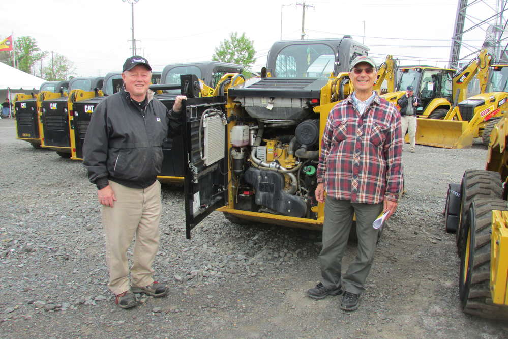 Bill Kelly (L), product support sales representative of Ransome CAT, and Tom Caracio of WGP Inc., Wind Gap, Pa., check out the engine of a Caterpillar 236D skid steer.