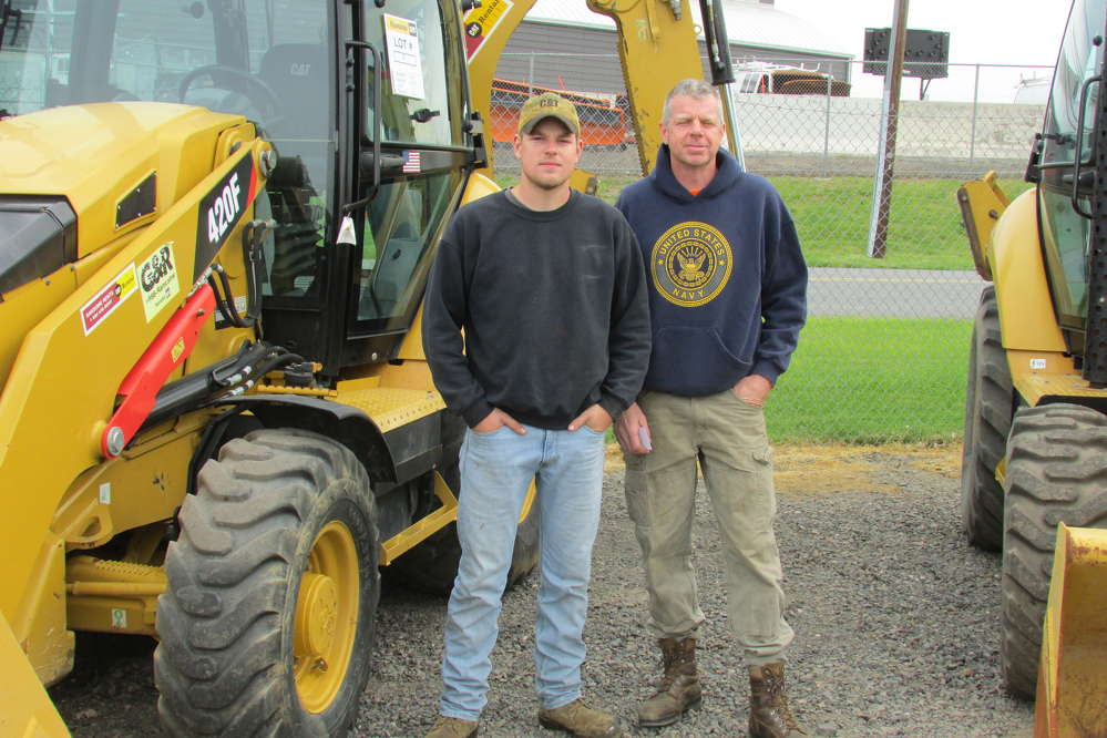 Noah (L) and Travis Newcomb, both of Cornell Construction, Woodbury, N.J., may be interested in purchasing a Caterpillar 420F wheel loader.
