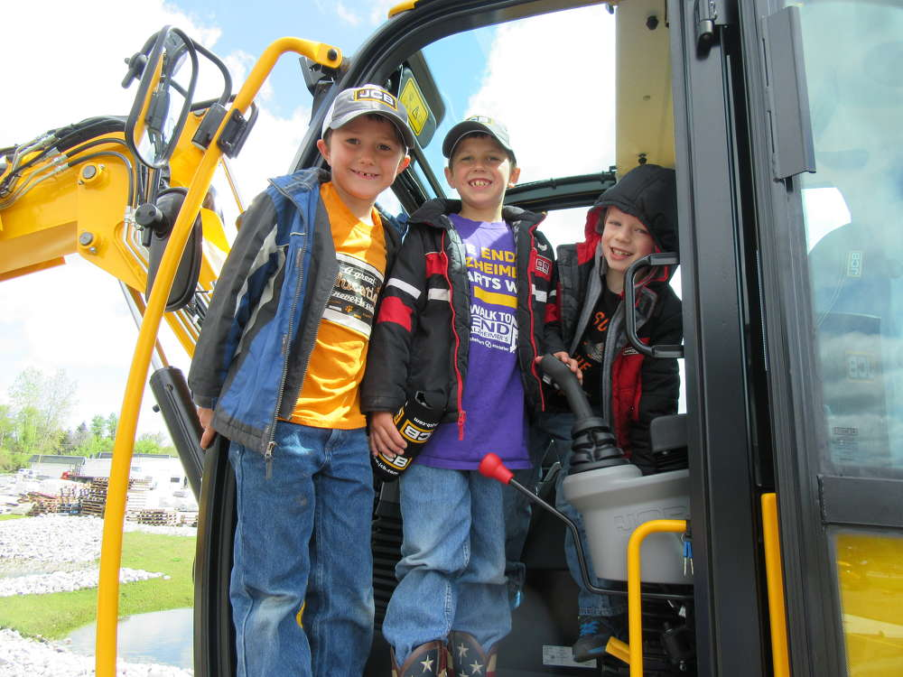 (L-R): Terry McConnell of Terry McConnell Excavating LLC brought his grandkids, Dillon and Grayson Vogel and Hunter Toney, to get a close up look at the JCB equipment and enjoy the festivities.