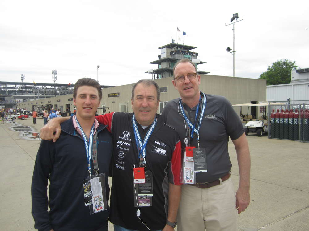 (L-R): The father and son team of Robby and Ted Roth of Erman Corporation and Bill McNamara, Howell Tractor and Equipment, head to the garage area to see the #15 car driven by Graham Rahal.