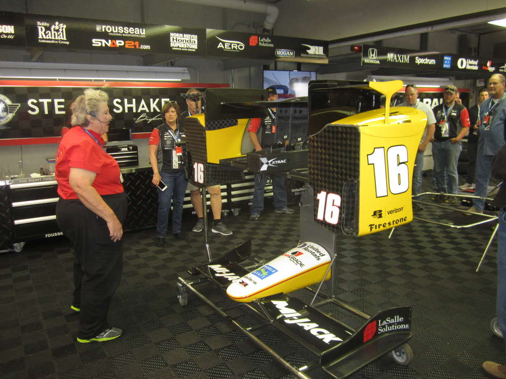 IndyCar afficionado Mary Mendez (L) talks with Howell Tractor's customers during the VIP Garage & Pit Tour.