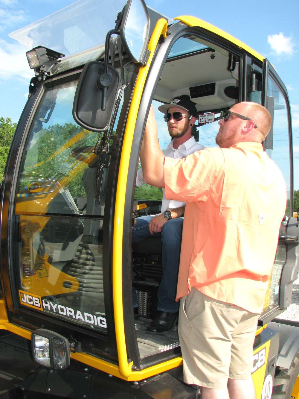 Jeffrey Treynor (L) of Ocean Woods Landscaping, Hilton Head Island, S.C., and Jarred Mayse of CSA in Sea Pines, Hilton Head Island, S.C., check out the cab of the new JCB Hydradig 110w wheeled excavator.