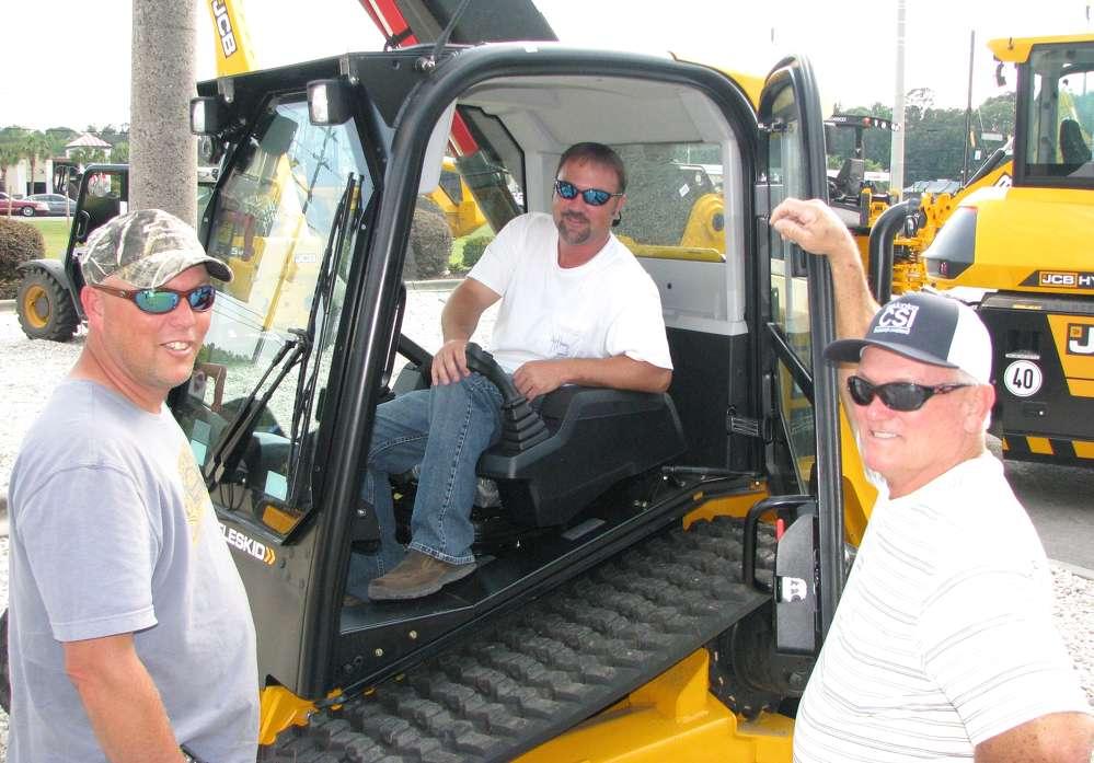 (L-R): Roger Clark Jr., Jeremy Clark and Roger Clark, Sr., all of Clark Services Richmond Hill, Ga., look over the JCB Teleskid.