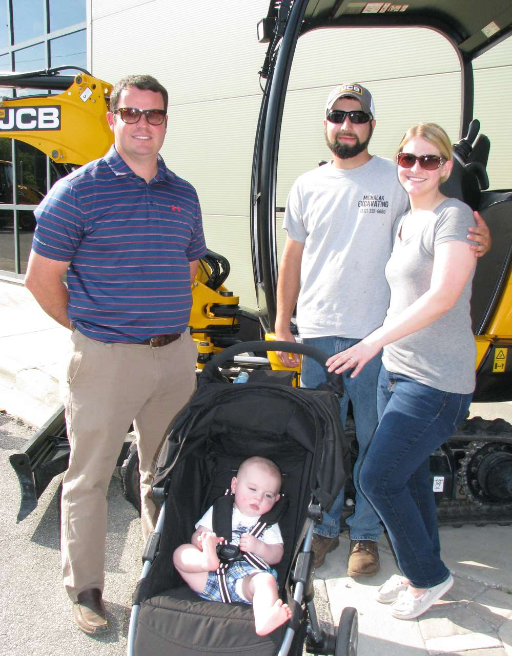 (L-R): Tony Davis, Low Country JCB salesman, talks with Brad and Gina Michalak, both of Michalak Excavating, Guyton, Ga., and the next generation owner, Jace Michalak.