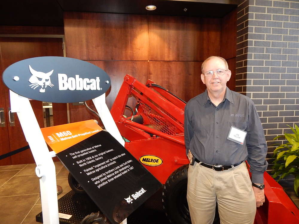 Cy Keller's son, Joe Keller, stands next to one of the company's first loaders, a M60 self propelled loader.