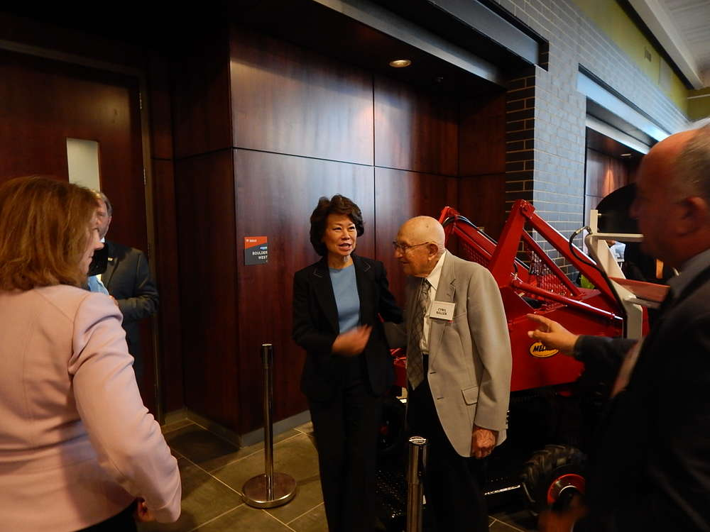Elaine Chao, United States Secretary of Transportation, greets Cyril Keller, skid steer inventor.