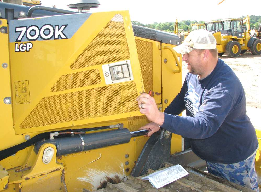 John Bollinger of Pioneer Equipment, Savannah, Ga., does a brief inspection of the power plant of a John Deere 700K dozer.