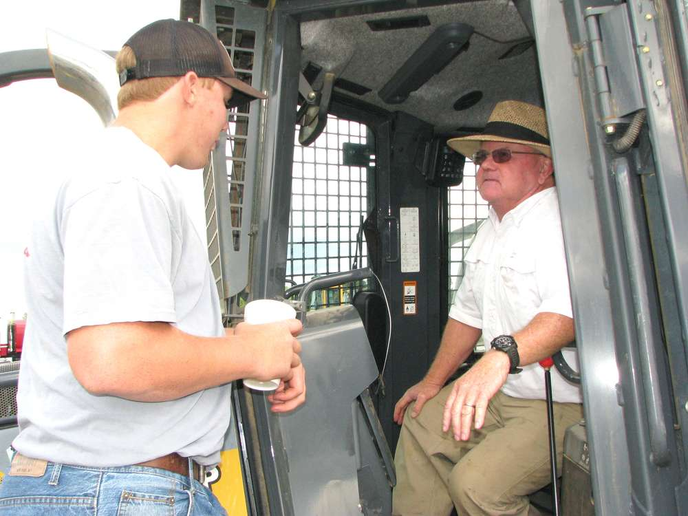 Checking out the cab of a John Deere 650K dozer in the sale lineup is Hugh (L) and Rush Cameron of Cameron's Quail Preserve, Aliceville, Ala